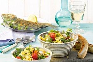 Fettuccine-Salat mit Cocktailtomaten, Mini-Mozzarellakugeln, Rucola und gerösteten Pinienkernen